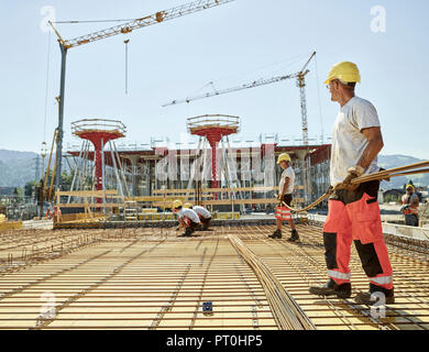 Workers on construction site preparing iron rods - Stock Photo