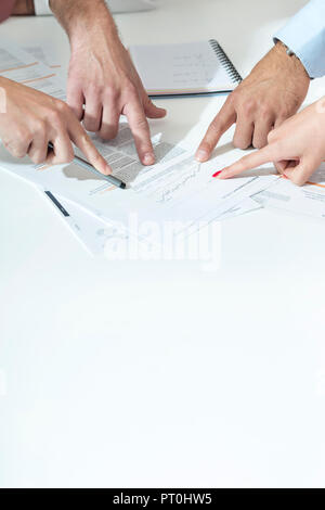 Poland, Warzawa, four hands of businessmen pointing at paper - Stock Photo