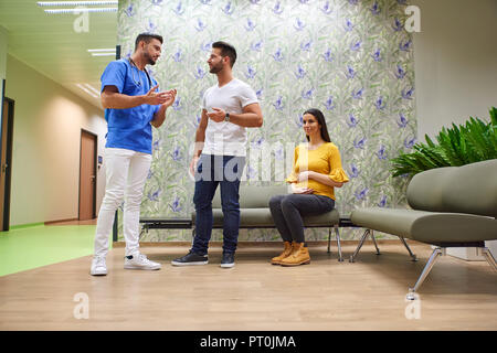 A handsome male doctor consulting with a young pregnant couple in the doctors waiting room. - Stock Photo