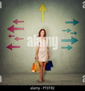 Full length portrait of cute girl carrying paper bags and thinking about next shopping destination. Confused young woman and arrows pointed to differe - Stock Photo