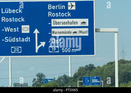 Autobahn sign in Germany Caption on German - city names Berlin, Rostock, Lübeck - Stock Photo