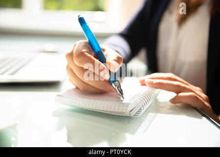 Close-up Of A Businesswoman's Hand Writing Note With Pen In Diary Over Desk - Stock Photo