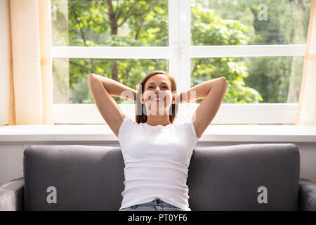 Portrait Of A Relaxed Woman Sitting On Sofa - Stock Photo