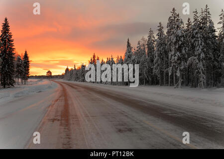 Sunrise view in winter on the way from Rovaniemi in Finland to Kiruna in Sweden road travel. - Stock Photo
