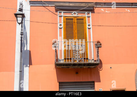 Traditional Italian door with shutters, metal balcony Italy, orange brown wall over shop, old fashioned concept, ornate,  wooden shutter doors - Stock Photo