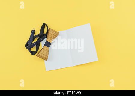 White greeting card with copy space and wooden tied bow on yellow background. Flat lay above view. Happy Boss day, Birthday, Father's day greeting moc - Stock Photo