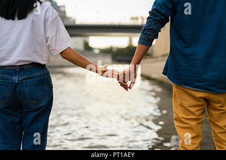 France, Paris, couple holding hands at river Seine - Stock Photo