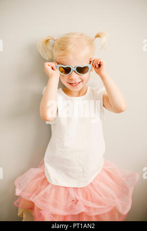 Portrait of blond little girl putting on heart-shaped sunglasses - Stock Photo