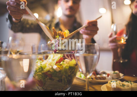 Man serving salad at dinner with family and friends - Stock Photo