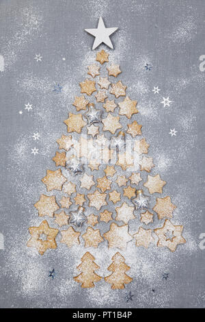 Star-shaped biscuits and Christmas baubles forming Christmas Tree on grey background - Stock Photo