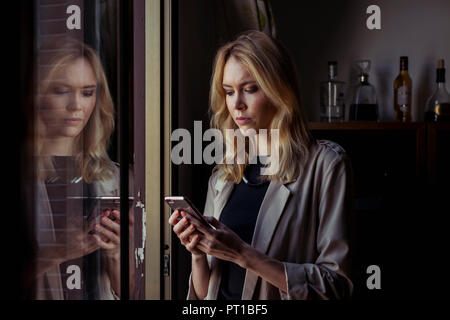 Portrait of blond young woman looking at cell phone - Stock Photo