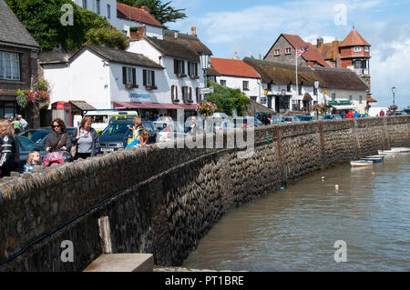 View of the quay wall along the shopping frontage filled with people on a sunny day in Lynmouth North Devon - Stock Photo