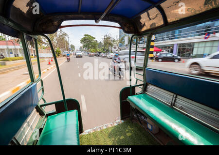 View of traffic on a street from the back of a songthaew (pick-up or small truck with benches along the sides) in Vientiane, Laos, on a sunny day. - Stock Photo