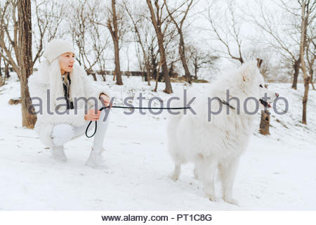 White dressed young woman with white dog in the snow watching something - Stock Photo
