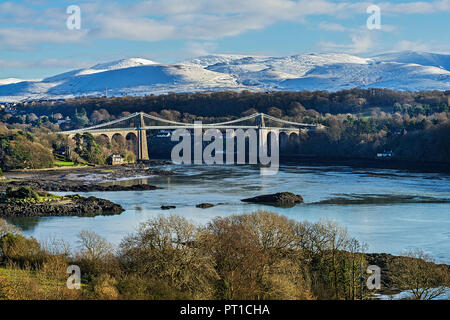 Menai Suspension Bridge designed by Thomas Telford viewed from Anglesey across the Menai Strait with snow capped hills in the background North Wales U - Stock Photo