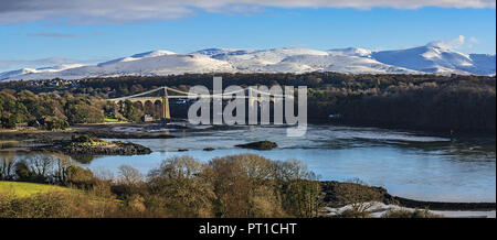 Menai Suspension Bridge designed by Thomas Telford viewed from Anglesey across the Menai Strait with snow capped hills in the background North Wales - Stock Photo