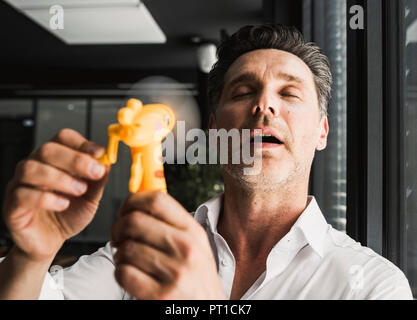 Businessman using hand fan in office - Stock Photo