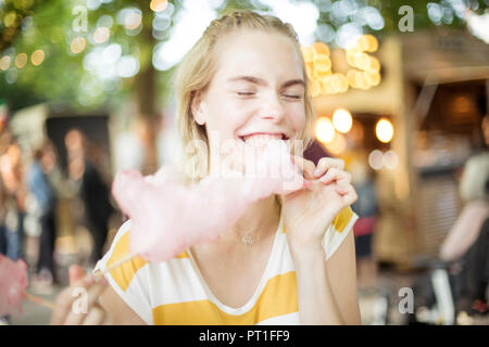Portrait of young woman eating pink candy floss on streetfood festival - Stock Photo