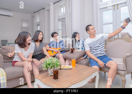 Group of friends take picture with smartphone and sing song with guitar at home. Concept about friendship, home entertainment and people - Stock Photo