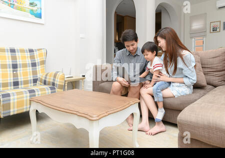 Happy family with little kids enjoying using application on laptop together, Son is watching video or doing internet shopping at home, edcation concpe - Stock Photo