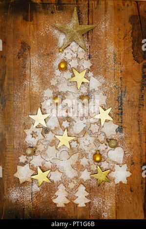 Christmas cookies and golden Christmas baubles and stars forming Christmas Tree on wood - Stock Photo