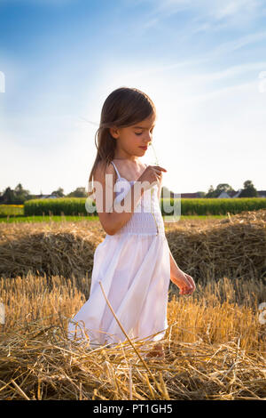 Little girl standing in havested field smelling flower - Stock Photo
