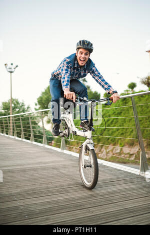 Young man doing tricks with a folding bike - Stock Photo
