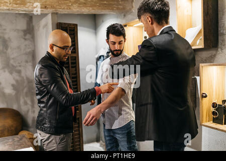 Two men working on new stylish look for handsome man in showroom - Stock Photo