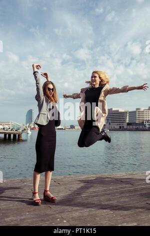 Spain, Barcelona, two fashionable young women having fun - Stock Photo