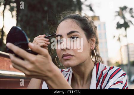 Portrait of woman applying mascara - Stock Photo
