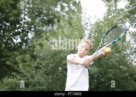 Portrait of blond boy playing tennis - Stock Photo
