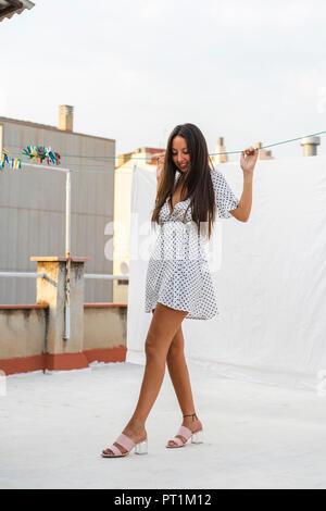 Fashionable young woman on roof terrace - Stock Photo