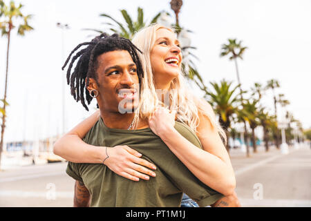 Spain, Barcelona, portrait of multicultural young couple on promenade - Stock Photo
