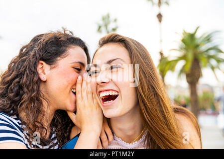 Two happy female friends whispering and laughing - Stock Photo