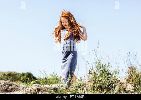 Netherlands, Zandvoort, redheaded girl walking in dunes - Stock Photo