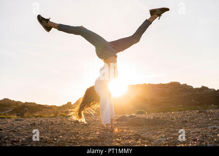 Young woman at the beach, doing handstand at sunset - Stock Photo