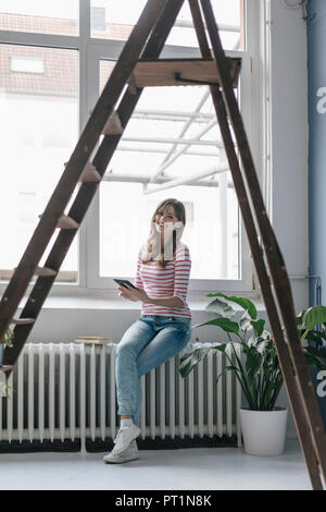 Woman sitting on radiator in her new home, reading e-book, surrounded by plants - Stock Photo
