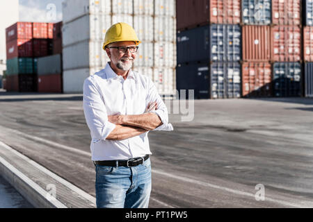 Businessman at cargo harbour, wearing safety helmet, arms crossed - Stock Photo