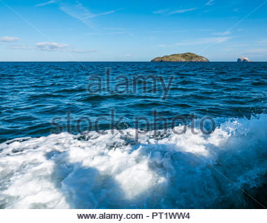 Firth of Forth, Scotland, United Kingdom, 5th October 2018. Boat wake in sea looking towards Craigleith Island and Bass Rock on the horizon on sunny day with blue sky - Stock Photo