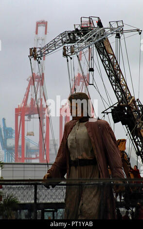 Merseyside, UK. 5th October 2018. The Giants in Liverpool at New Brighton.  New Brighton, Wirral, UK. 5th October 2018. On a gloomy autumn morning The Giant makes his way along the Marine Drive at New Brighton on The Wirral on the opposite side of the River Mersey from the cranes of Seaforth docks Credit: Colin Wareing/Alamy Live News - Stock Photo