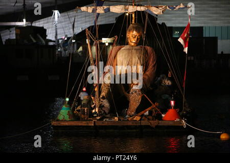 Liverpool, UK. 5 October 2018.  Giant puppet resting on a floating raft at the Albert Dock, Liverpool. Credit: Ian Fairbrother/Alamy Live News - Stock Photo