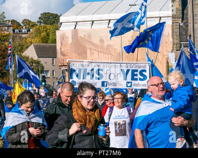 Holyrood, Edinburgh, Scotland, United Kingdom, 6th October 2018. All Under One Banner (AUOB) Scottish March and Rally for Independence, with supporters walking down the Royal Mile to Holyrood Park for a rally. AOUB is a pro-independence campaign for whose core aim is to march at regular intervals until Scotland achieves independence. Independence supporters wave saltire flags. People march with a NHS for Yes banner - Stock Photo