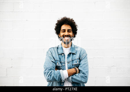 Portrait of grinning young man in front of white wall - Stock Photo