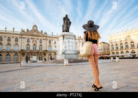 Young woman tourist enjoying beautiful morning view on the central square traveling in Nancy city in France - Stock Photo