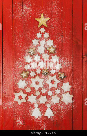 Christmas cookies and star-shaped Christmas baubles forming Christmas tree on red wooden background - Stock Photo