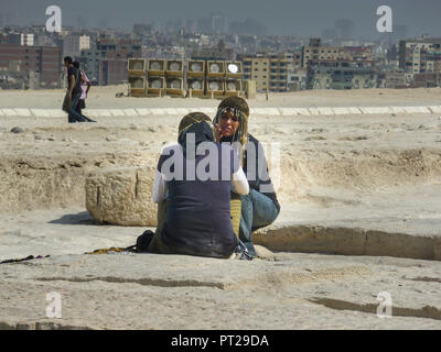 Cairo Egypt: October 20th 2011 . Typical pyramid women street vendors sitting on a step next to the Great Pyramid of Giza. - Stock Photo