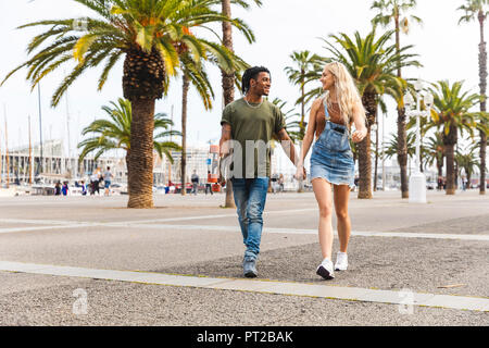 Spain, Barcelona, multicultural young couple walking hand in hand on promenade - Stock Photo