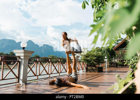 Laos, Vang Vieng, Young couple doing acro-yoga on a terrace - Stock Photo