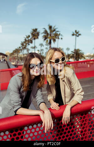 Portrait of two fashionable young women wearing sunglasses - Stock Photo