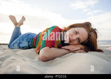 Redheaded woman lying in sand on the beach - Stock Photo